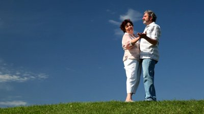 stock-footage-mature-couple-cute-dance-on-green-grass-against-sky-in-summer